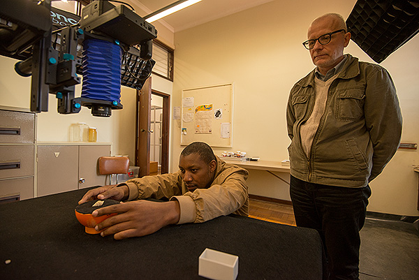 Dr Igor Muratov looks on as Africa Media Online Digitization Assistant, Timothy Zuma, lines up a mollusk specimen. Dr Muratov gave valuable input in the correct alignment of such specimens.