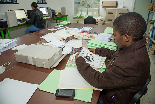 Africa Media Online team member, Steven Ntsikithi, prepares a folder of items dividing various items into one of three workflows - rare and fragile manuscripts are captured by an overhead camera, bound manuscripts by a v-cradle capture device, and plain paper by the Scamax machine
