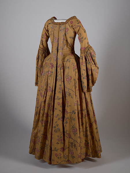 Dress of Indian chintz, probably made at the Cape. Note the use of the indigo in some of the floral sprigs. Coromandel Coast, India, c.1775. The Indian method of applying designs on to cotton was complicated, and included the application of various coats of resist paste (in this case, beeswax) and mordants, alternated with dippings into madder red or indigo blue dyebaths, and a final  direct application of yellow dye where needed. Presented by Marianne Pfeiffer, Iziko Soc Hist. L67/153