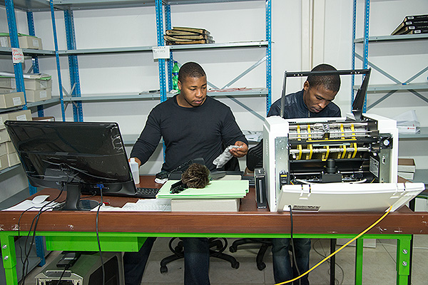 Nkanyiso Ngcobo and Phelelani Ntsikithi cleaning the Scamax machine. The belt-driven form-feed scanner is very gentle on paper and so is ideal when used in an archive with mixed manuscripts like the ANC Archive. Operated two shifts a day, this scanner captured over 1.3 million pages in about a year and a half.