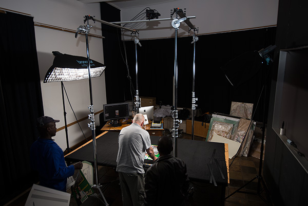Africa Media Online photographer Scott Cronwright assisted Lunga Poni (NAHECS) and Sphelele Ntsikithi (AMO) digitised oversized flat materials including posters and banners. The Phase One XF camera is suspended on the digitisation rig we built. It is set to 150 ppi, the correct setting to be Metamorfoze compliant for this size material.