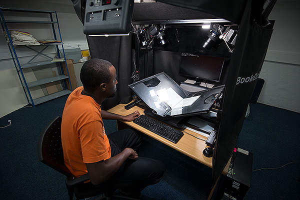 Kulu Mushaka operating Africa Media Online's modified Atiz machine on-site at NAHECS, University of Fort Hare Alice Campus. The machine is a v-cradle capture device that enables the capture of bound manuscripts. To get a higher quality output from the machine we customised the lights and put Zeiss lenses on the two Canon 5D Mk II cameras. We also added a screen that improved operator comfort.
