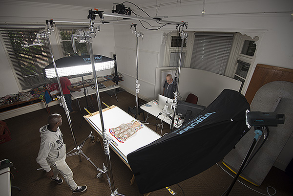 Sandile Mhlongo, who has just loaded a flat object onto the capture surface, waits for Scott Cronwright to capture a flat object while Timothy Zuma prepares the next object. The object being captured is a beaded waistcoat. It is illuminated evenly by our Broncolor lights.