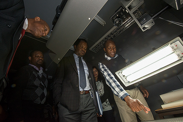 A member of the Wits University digitisation team explains the digitisation technology that the University has available to Dr Daniel Adams, Chief Director: Department of Science and Technology (left) and Professor Zeblon Vilakazi, Deputy Vice-Chancellor, Research and Post-Graduate Affairs, Wits University (centre), while Ayodele O. Ladokun (left), Lecturer in Computer Literacy at the University of Fort Hare (second left) looks on during the official opening of the Wits-NRF Digitisation Capacity Development Initiative at the Wartenweiler Library 4th floor, University of the Witwatersrand.